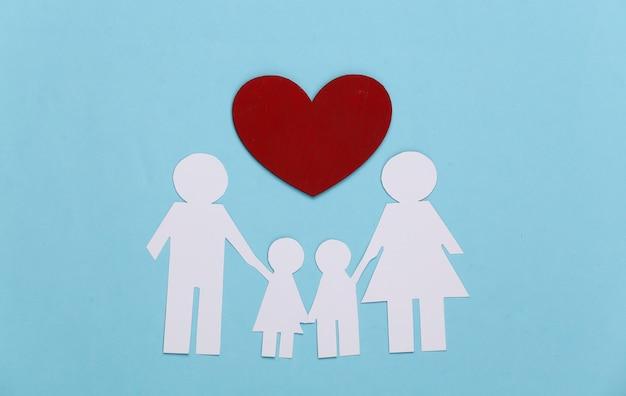 Família feliz de papel junto com um coração vermelho em azul