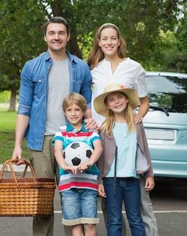 Família feliz de quatro com cesta de piquenique