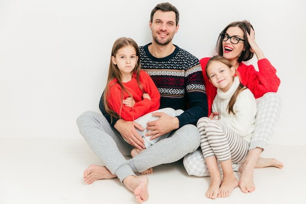 Família feliz de quatro membros: mulher morena atraente, seu marido e duas filhas pequenas sentam no chão