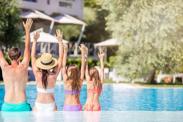 Família feliz de quatro na piscina ao ar livre