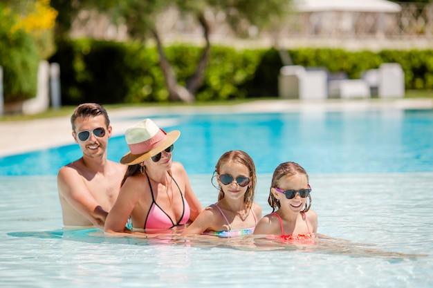 Família feliz de quatro na piscina