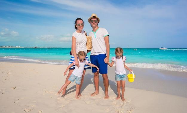 Família feliz de quatro na praia de férias tropicais