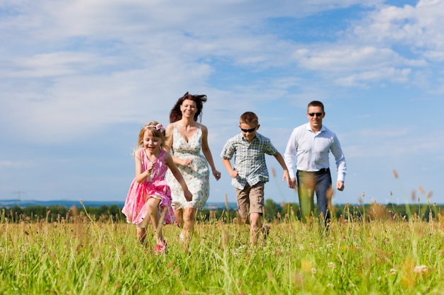 Família feliz, de quatro pessoas correndo na grama verde