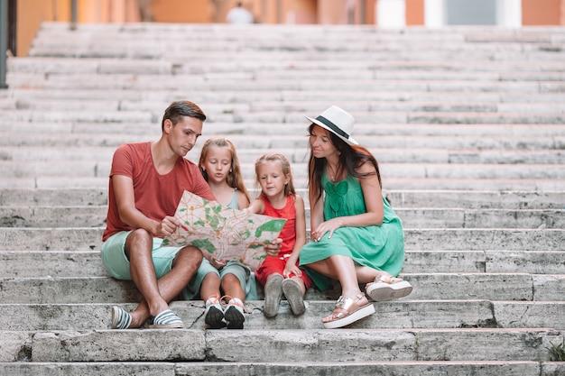 Família feliz de quatro pessoas em roma com mapa