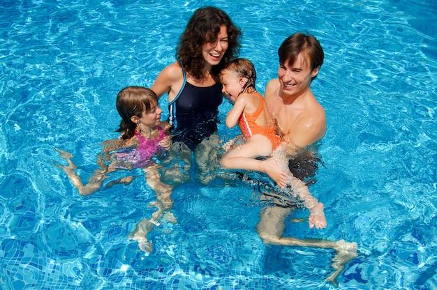 Família feliz, de quatro pessoas se divertindo na piscina