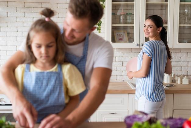 Família feliz de tiro médio na cozinha