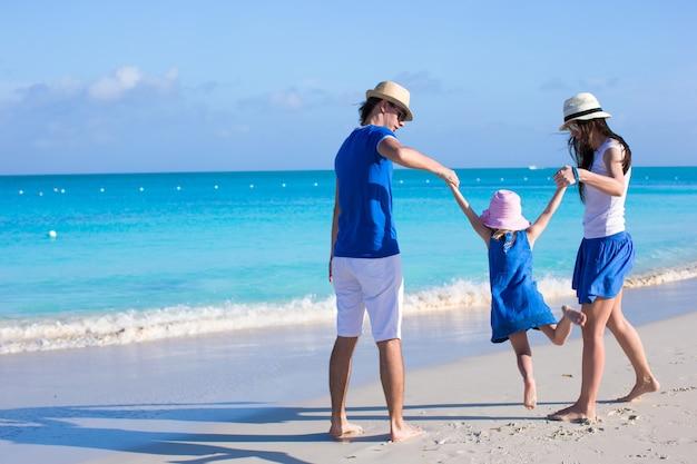 Família feliz de três curtindo férias na praia