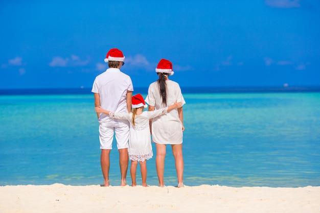 Família feliz de três em chapéus de papai noel durante as férias tropicais