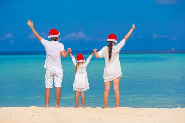 Família feliz de três em chapéus de papai noel na praia