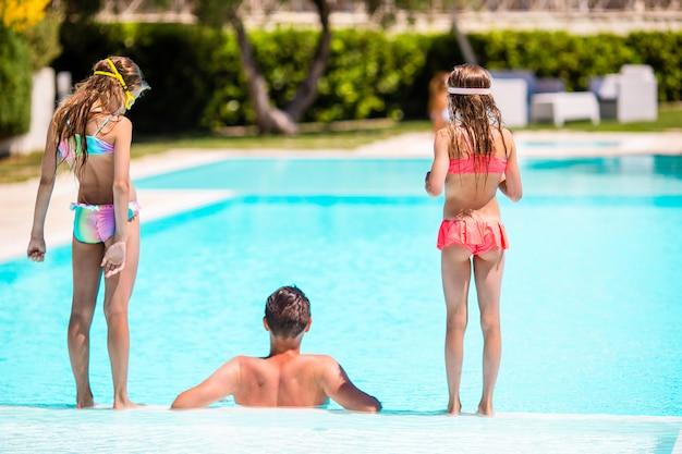 Família feliz de três na piscina ao ar livre