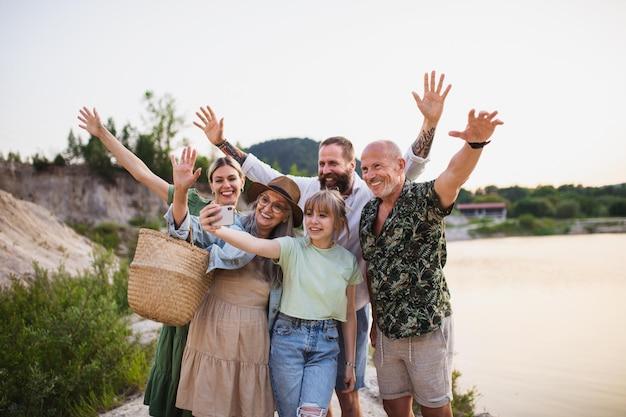Família feliz de várias gerações em caminhada nas férias de verão, tomando selfie.
