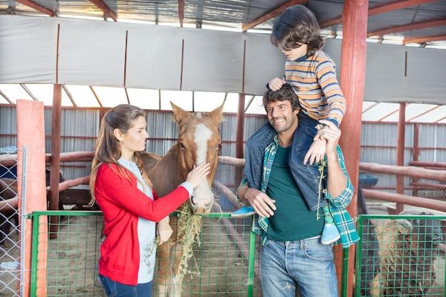Família feliz de visitar o cavalo no estábulo