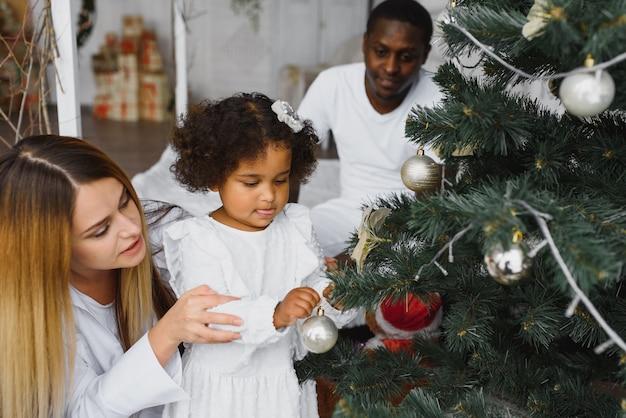 Família feliz decorando a árvore de natal