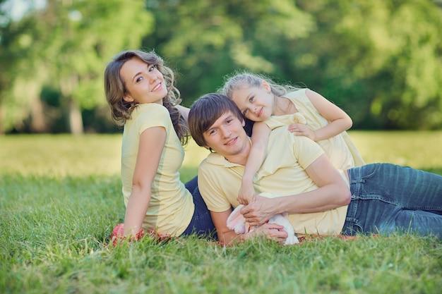 Família feliz deitada na grama do parque.