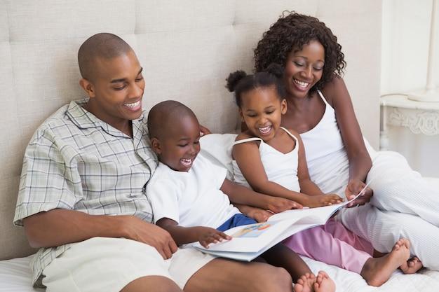 Família feliz deitada no livro de leitura da cama