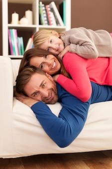 Família feliz deitada no sofá