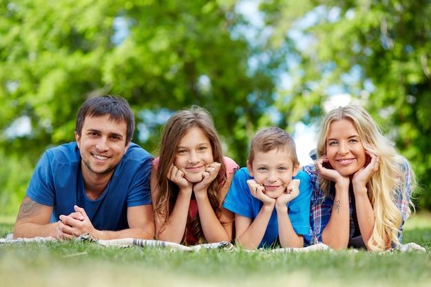 Família feliz deitado em uma fileira