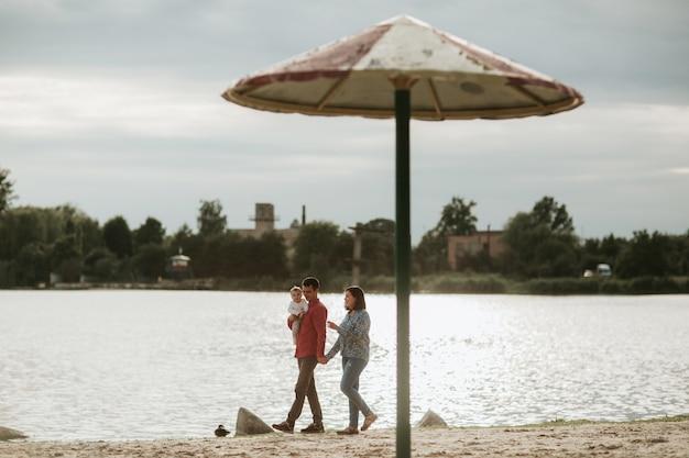 Família feliz descansando à beira do lago
