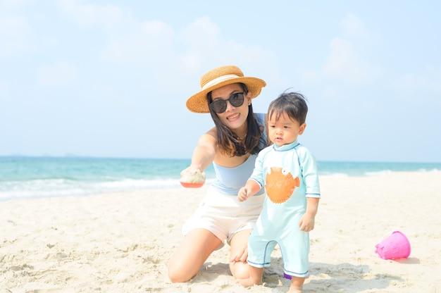 Família feliz descansando na praia no verão, os pés da mãe e do bebê na espuma do mar na água do sol estão se movendo