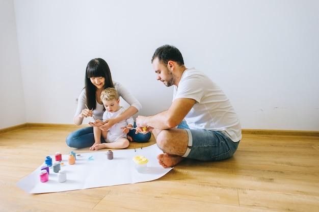 Família feliz, desenhando no papel no chão em parquet com um gato