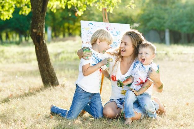 Família feliz desenho ao ar livre. jovem mãe se divertindo com seus filhinhos