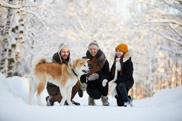 Família feliz, desfrutando de passeio com cachorro