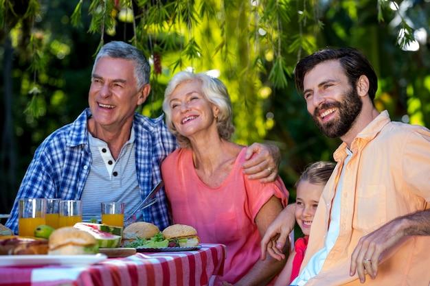 Família feliz desfrutando enquanto refeição no quintal