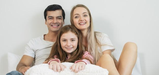 Família feliz do retrato que passa o tempo junto na cama no quarto.