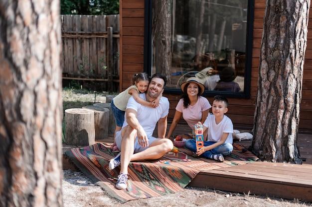 Família feliz, dois filhos e seus pais, descansando perto de uma casa de campo na floresta, curtindo o tempo que passamos juntos durante as férias de verão e feriados