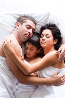 Família feliz dormindo na cama