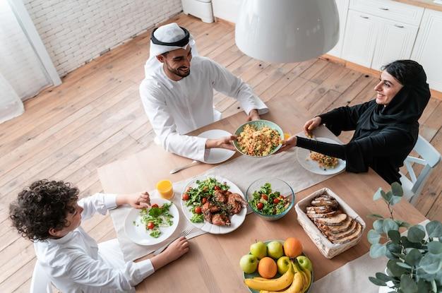 Família feliz dos emirados árabes unidos comendo juntos e comemorando os feriados do dia nacional