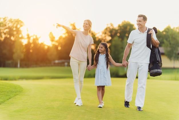 Família feliz dos jogadores de golfe anda pelo gramado do por do sol.