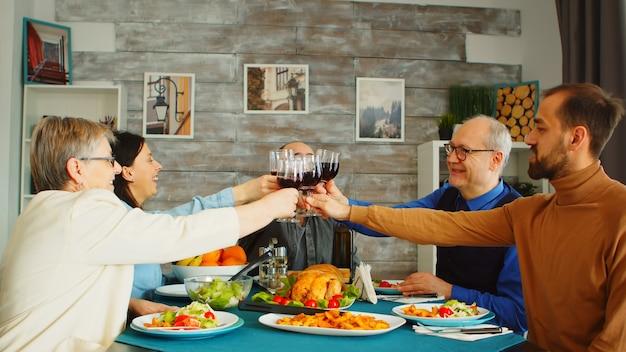 Família feliz durante o almoço, brindando com vinho tinto. amigos e família no jantar de domingo