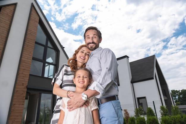 Família feliz e alegre se abraçando enquanto ficavam juntos na frente da casa