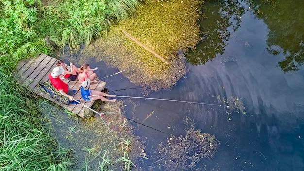 Família feliz e amigos pescando juntos ao ar livre perto do lago no verão, vista superior aérea de cima