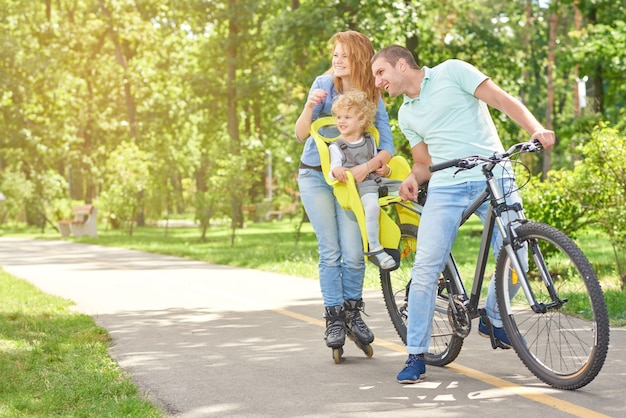 Família feliz e ativa, patinando e andando de bicicleta no parque no verão.