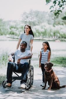 Família feliz e cão paraplégico ao ar livre