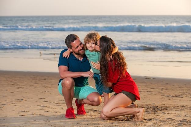 Família feliz e criança apreciando o pôr do sol na praia. lazer de verão.