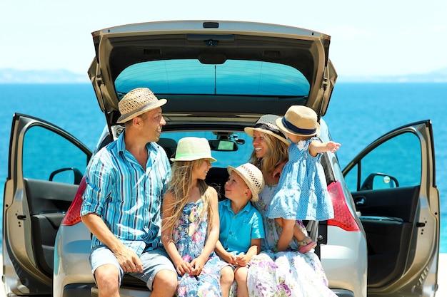 Família feliz e feliz de carro à beira-mar