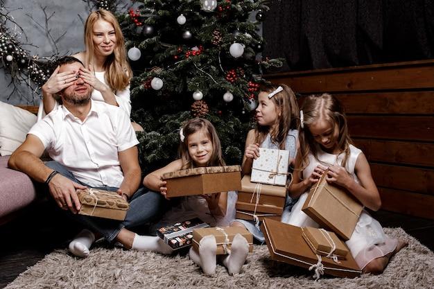 Família feliz e fofa com três filhos trocando presentes debaixo da árvore de natal no tapete.