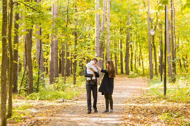 Família feliz e jovem relaxando juntos na natureza dourada e colorida do outono.