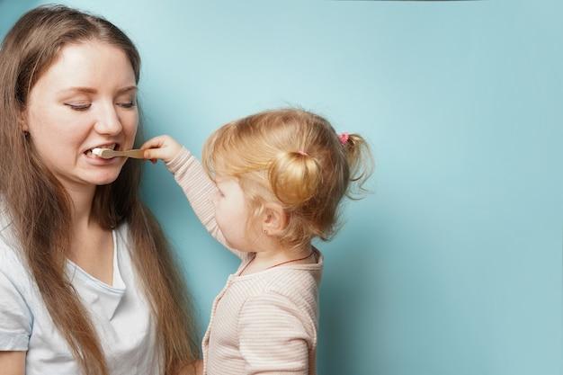 Família feliz e saúde. mãe e filha criança menina escovando os dentes na superfície azul