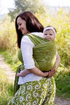 Família feliz e sorridente com a mãe e a filha em uma tipóia verde, bebê vestindo