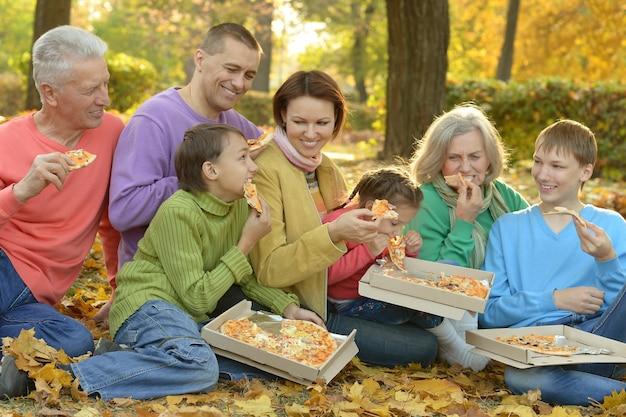 Família feliz e sorridente comendo pizza no parque outono