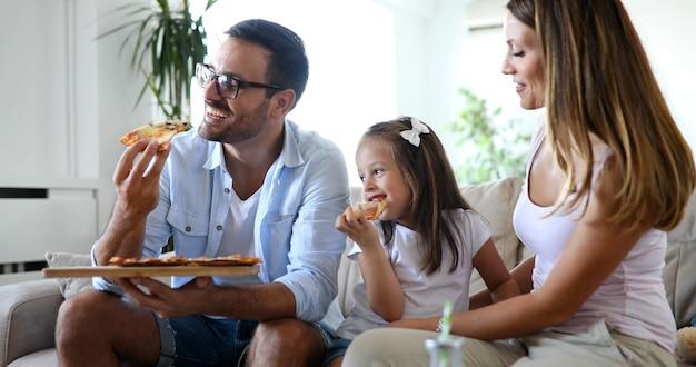 Família feliz e sorridente compartilhando pizza em casa