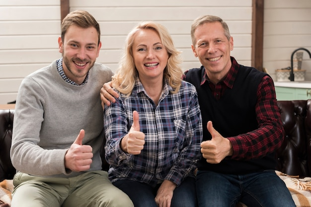 Família feliz e sorridente posando ao mesmo tempo dando polegares para cima