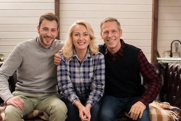 Família feliz e sorridente, posando no sofá