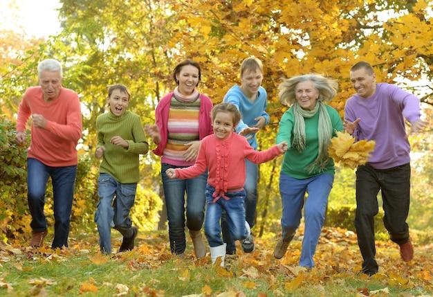 Família feliz e sorridente relaxando na floresta de outono