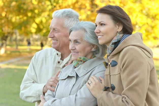 Família feliz e sorridente relaxando no parque de outono
