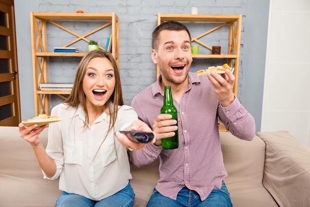 Família feliz e surpresa assistindo filme e comendo pizza com cerveja